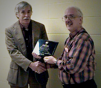Dr. Harry Perlstadt, Commissioner, presenting a commemorative plaque to Dr. Jim Sherohman, Director of the first Applied Sociology program to be accredited